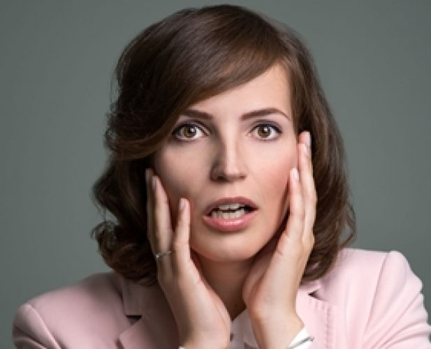44085472 - young woman reacting in shock and horror with her mouth agape and hands raised to her cheeks as she looks sideways to the left of the frame, over grey