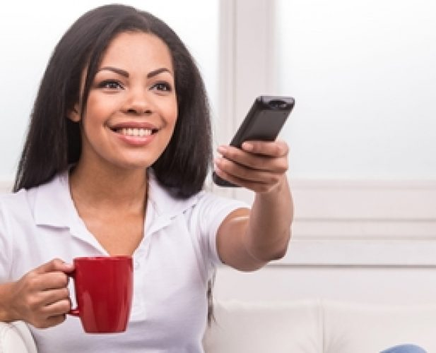 30648822 - woman watching tv at home and holding a remote control. smiling woman on couch changing tv programme